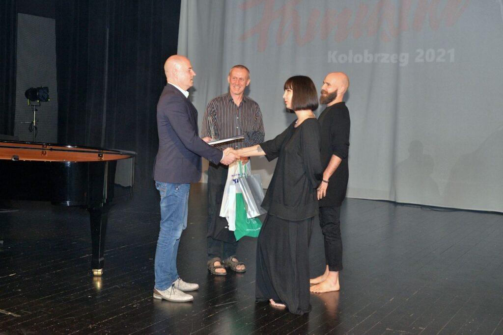 Zwycięzcy konkursu Paulina Lenda i Piotr Kozub odbierają nagrodę od Przemysława Tejkowskiego